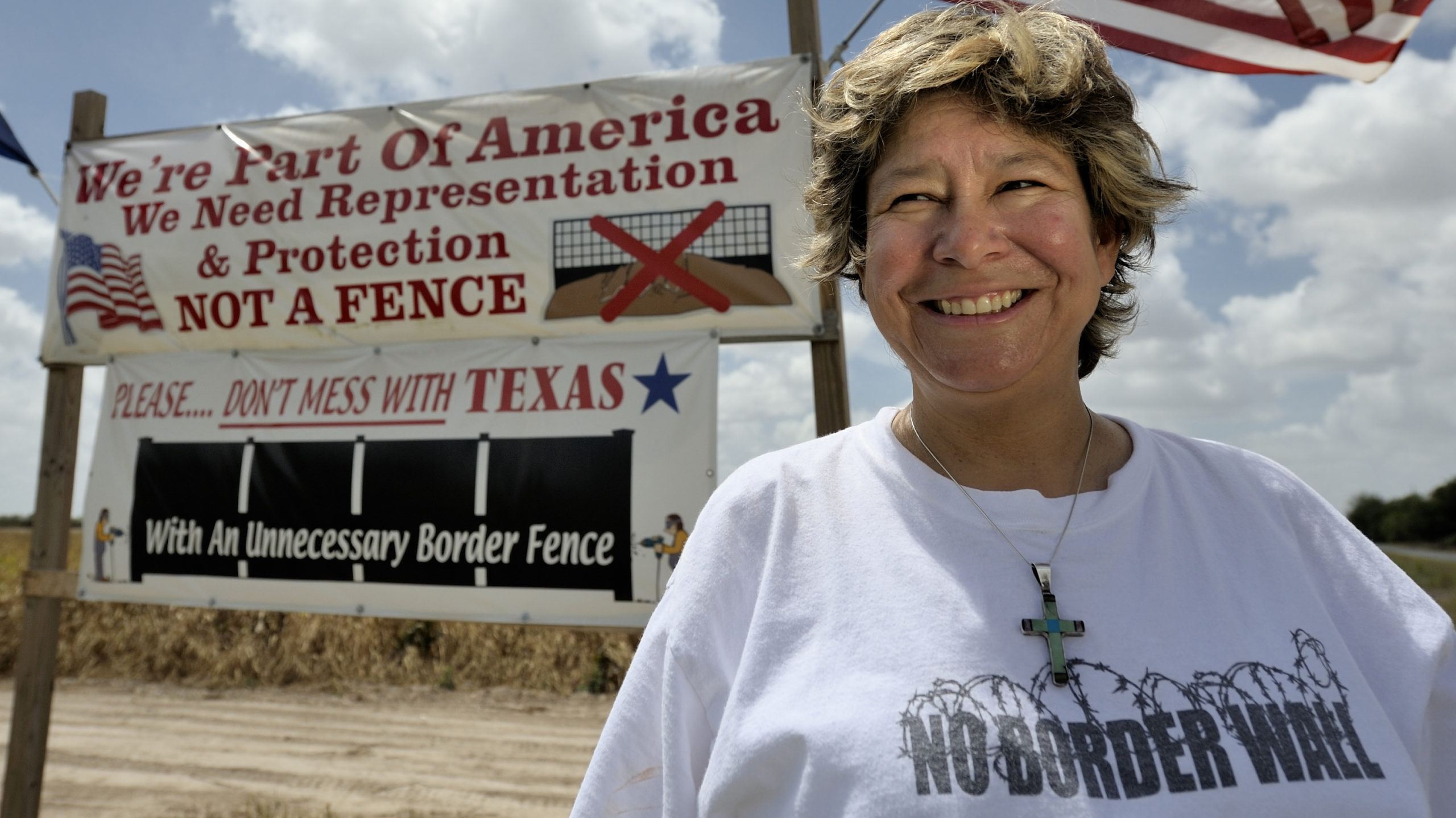 "Cindy Johnson, white female deaconess, stands in front of a white sign by the Texas / Mexican boarder which reads: ""We're Part of America, We need Representation & Protection, NOT A FENCE"" and another sign which says, ""Please... DON'T MISS WITH TEXAS, with an unncessary border fence."" Cindy is weraring a shirt that says, ""No Border Wall"" and a crucifix necklace. An American flag waves in the wind behind her."